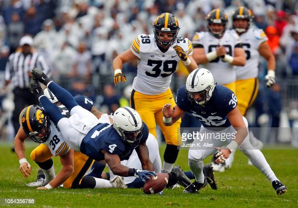 Nick Scott of the Penn State Nittany Lions and Jan Johnson attempt to recover a fumble against TJ Hockenson of the Iowa Hawkeyes on October 27 2018...