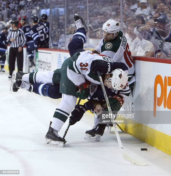 Nick Seeler of the Minnesota Wild battles Mathieu Perreault of the Winnipeg Jets in Game One of the Western Conference First Round during the 2018...