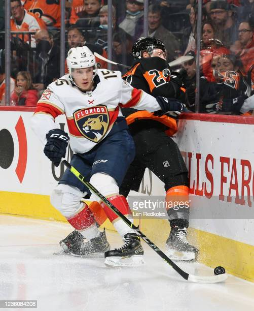 Nick Seeler of the Philadelphia Flyers battles for control of the loose puck along the boards with Anton Lundell of the Florida Panthers at the Wells...
