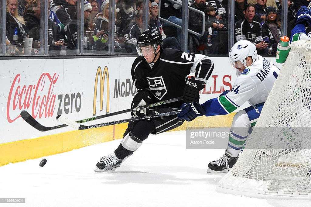 Nick Shore #21 of the Los Angeles Kings handles the puck against Matt Bartkowski #44 of the Vancouver Canucks at STAPLES Center on December 01, 2015 in Los Angeles, California.
