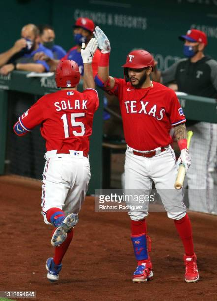 Nick Solak of the Texas Rangers high fives Anderson Tejeda after a solo home run in the fifth inning against the Baltimore Orioles at Globe Life...
