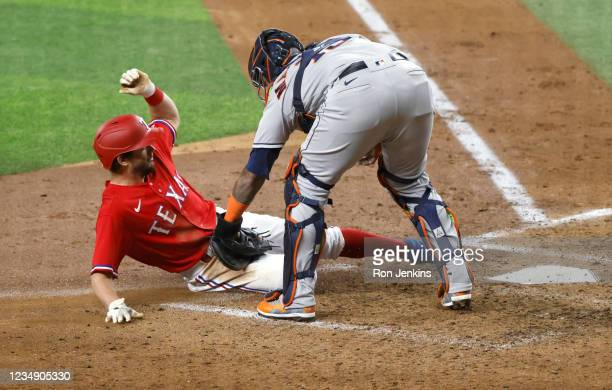 Nick Solak of the Texas Rangers is tagged out at home plate by Martin Maldonado of the Houston Astros during the fourth inning at Globe Life Field on...