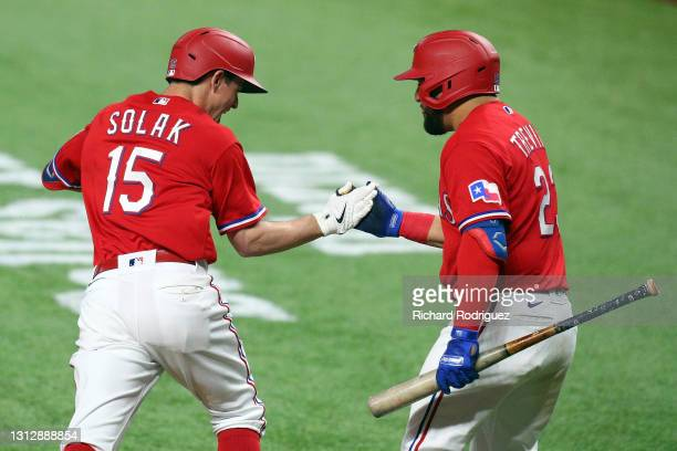 Nick Solak of the Texas Rangers slaps hands with Jose Trevino after a solo home run in the fifth inning against the Baltimore Orioles at Globe Life...