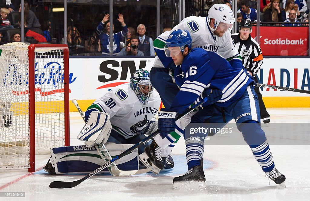 Nick Spaling #16 of the Toronto Maple Leafs looks to shoot the puck as Ryan Miller #30 and Alexander Edler #23 of the Vancouver Canucks defend during NHL game action November 14, 2015 at Air Canada Centre in Toronto, Ontario, Canada.