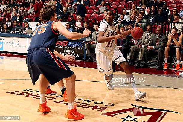 Nick Stover of the Loyola Marymount Lions drives against Jett Raines and Nikolas Skouen of the Pepperdine Waves in the first half of the game at...