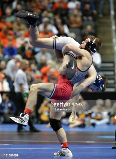 Nick Suriano of the Rutgers University Scarlet Knights lifts Dylan Duncan of the Illinois Fighting Illini during session one of the NCAA Wrestling...