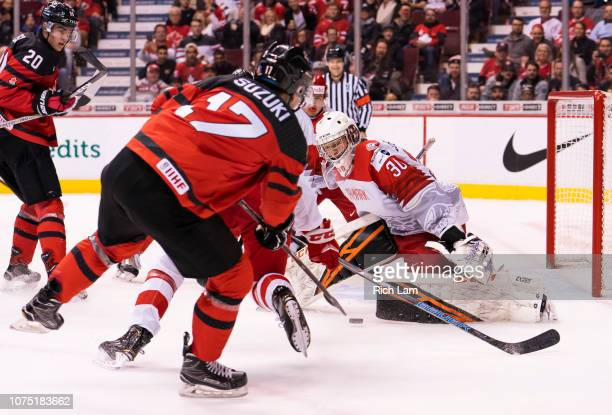 Nick Suzuki of Canada slides a pass across the front of the net and under goalie Mads Soegaard of Denmark in Group A hockey action of the 2019 IIHF...