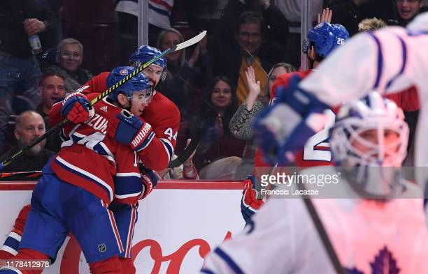 Nick Suzuki of the Montreal Canadiens celebrates with teammate Nate Thompson after scoring a goal against the Toronto Maple Leafs in the NHL game at...