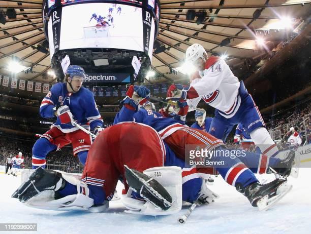 Nick Suzuki of the Montreal Canadiens checks Ryan Lindgren of the New York Rangers on top of Alexandar Georgiev during the third period at Madison...