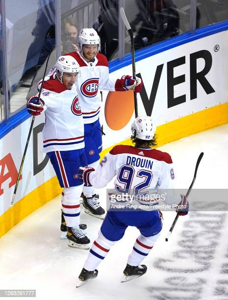 Nick Suzuki of the Montreal Canadiens is congratulated by teammates Jonathan Drouin and Joel Armia after he scored an unassisted goal in the second...