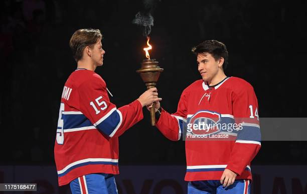 Nick Suzuki of the Montreal Canadiens passes the torch to teammate Jesperi Kotkaniemi in an opening ceremony prior to the NHL game against the...
