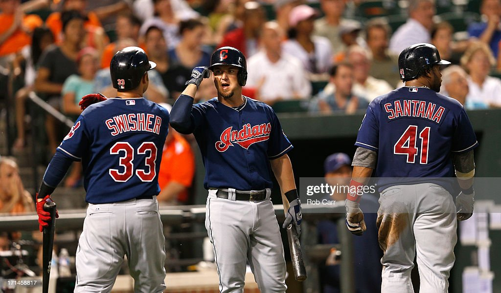 Nick Swisher #33 and Carlos Santana #41 celebrate with teammate Ryan Raburn #9 of the Cleveland Indians after they both scored during the sixth inning of the Indians 5-2 win at Oriole Park at Camden Yards on June 24, 2013 in Baltimore, Maryland.