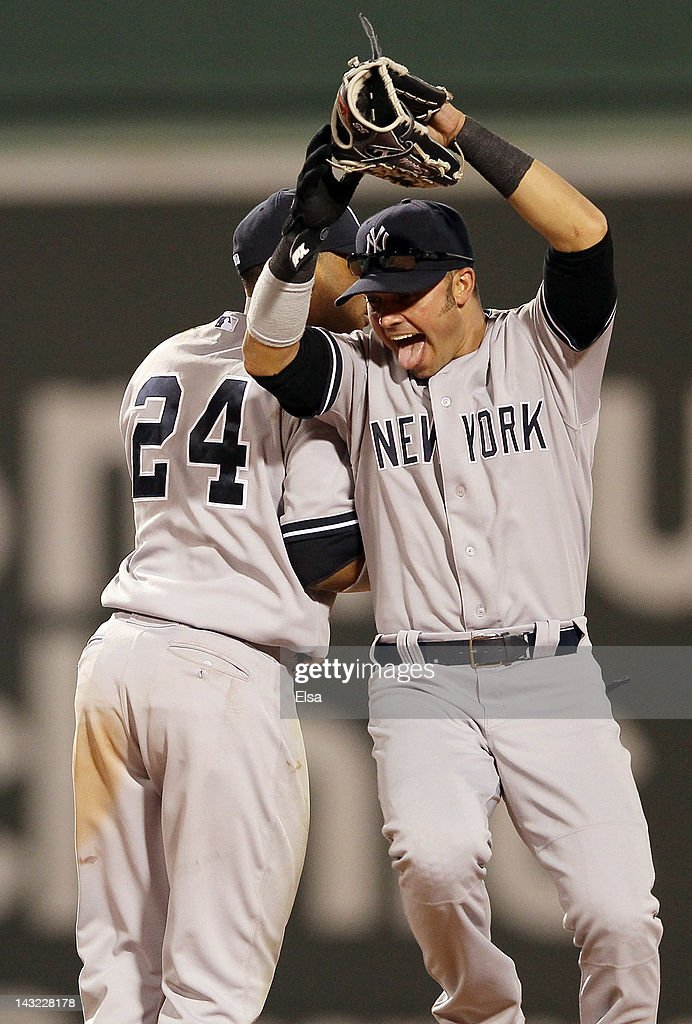 Nick Swisher #33 and Robinson Cano #24 of the New York Yankees celebrate the win over the Boston Red Sox on April 21, 2012 at Fenway Park in Boston, Massachusetts. The New York Yankees defeated the Boston Red Sox 15-9.