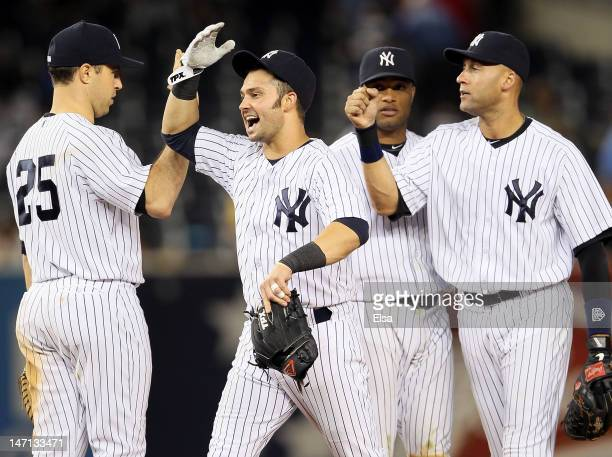Nick Swisher celebrates the win with Mark Teixeira Robinson Cano and Derek Jeter of the New York Yankees after the win over the Cleveland Indians on...