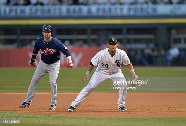 Nick Swisher of the Cleveland Indians leads off of first base as first baseman Jose Abreu of the Chicago White Sox gets ready for the pitch during...