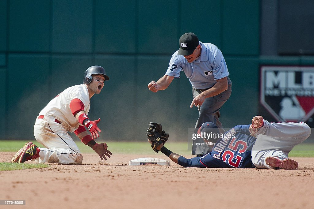 Nick Swisher #33 of the Cleveland Indians reacts as he is called out by second base umpire John Hirschbeck #17 as shortstop Pedro Florimon #25 of the Minnesota Twins holds on to the ball during the seventh inning at Progressive Field on August 25, 2013 in Cleveland, Ohio.