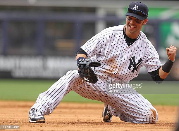 Nick Swisher of the New York Yankees celebrates after making the final out of the game by throwing out Charlie Blackmon of the Colorado Rockies...