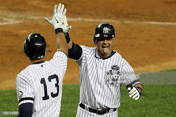 Nick Swisher of the New York Yankees celebrates with Alex Rodriguez after Swisher scored on a solo home run in the bottom of the seventh inning...
