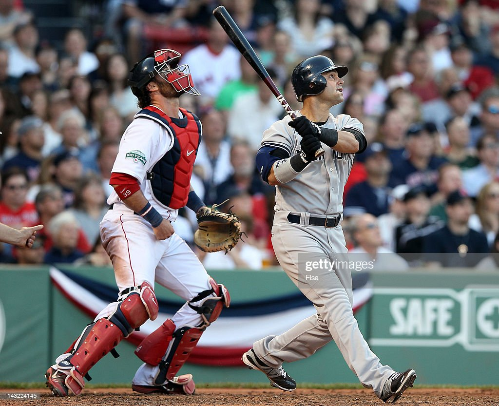 Nick Swisher #33 of the New York Yankees hits a grand slam as Jarrod Saltalamacchia #39 of the Boston Red Sox defends in the seventh inning on April 21, 2012 at Fenway Park in Boston, Massachusetts.
