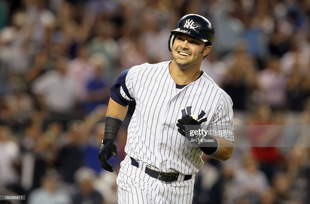 Nick Swisher #33 of the New York Yankees smiles at his dugout as he runs the bases after his third inning grand slam against the Texas Rangers at Yankee Stadium on August 13, 2012 in the Bronx borough of New York City.