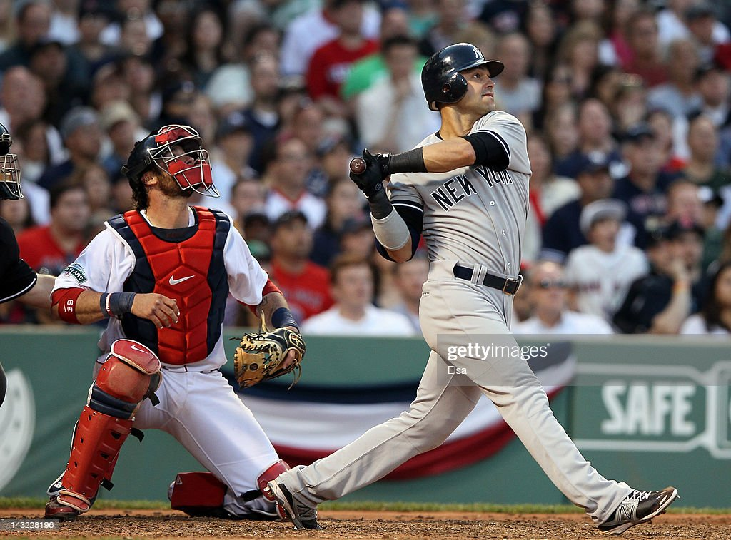 Nick Swisher #33 of the New York Yankees watches his hit as Jarrod Saltalamacchia #39 of the Boston Red Sox defends on April 21, 2012 at Fenway Park in Boston, Massachusetts.