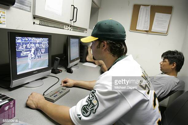 Nick Swisher of the Oakland Athletics looks at video alongside Keiichi Yabu before the game against the Seattle Mariners at McAfee Coliseum on June...