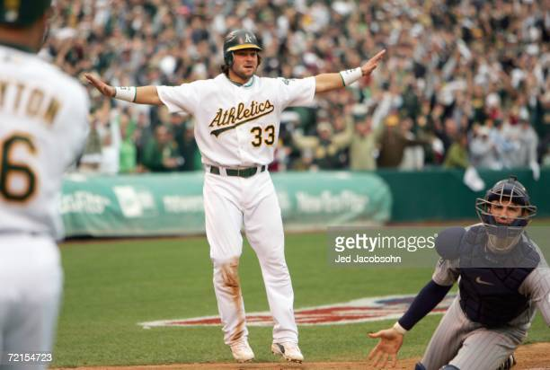 Nick Swisher the Oakland Athletics motions he is safe after sliding home against the Minnesota Twins to win game three of the American League...