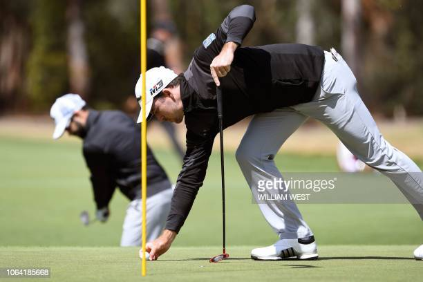 Nick Taylor of Canada marks his ball as teammate Adam Hadwin prepares to chip onto the green on the first day of the World Cup of Golf at the...