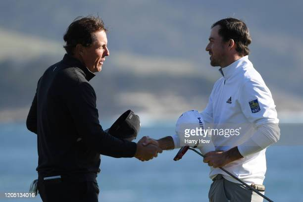 Nick Taylor of Canada shakes hands with Phil Mickelson of the United States on the 18th green after winning the ATT Pebble Beach ProAm at Pebble...