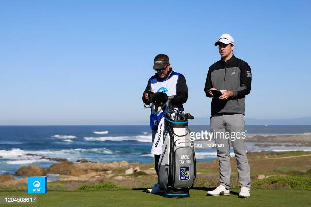 Nick Taylor of Canada talks with his caddie before playing his shot from the 13th tee during the during the first round of the ATT Pebble Beach ProAm...
