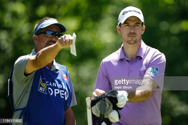 Nick Taylor of Canada talks with his caddie on the seventh hole during the first round of the RBC Canadian Open at Hamilton Golf and Country Club on...