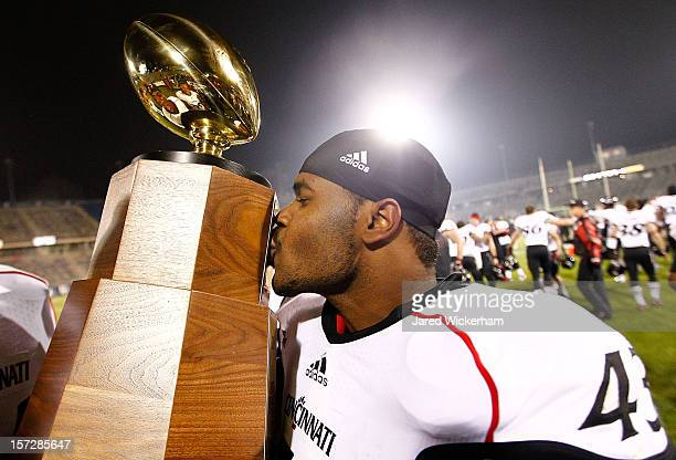 Nick Temple of the Cincinnati Bearcats kisses the Big East Championship trophy following their 34-17 win against the Connecticut Huskies which led to...
