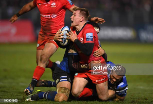 Nick Tompkins of Saracens is tackled by Francois Louw of Bath Rugby and Jamie Roberts of Bath Rugby during the Gallagher Premiership Rugby match...