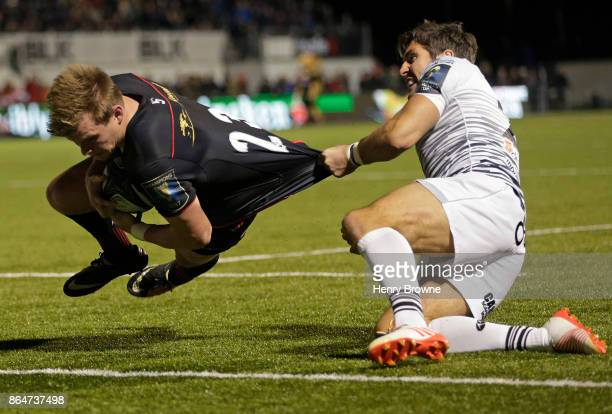 Nick Tompkins of Saracens scores a try despite the efforts of James Hook of Ospreys during the European Rugby Champions Cup match between Saracens...