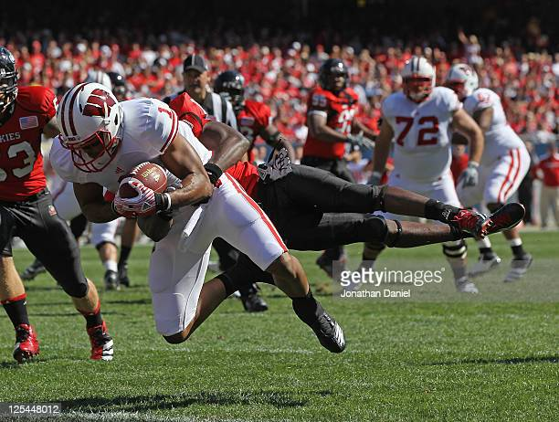 Nick Toon of the Wisconsin Badgers catches a touchdown pass as Jimmie Ward of the Northern Illinois Huskies tries to bring him down short of the goal...