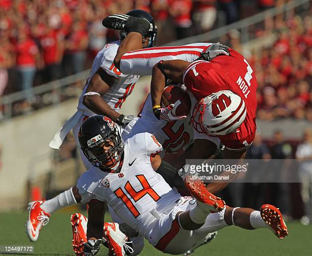 Nick Toon of the Wisconsin Badgers is upended by Jordan Poyer and Michael Doctor of the Oregon State Beavers at Camp Randall Stadium on September 10...
