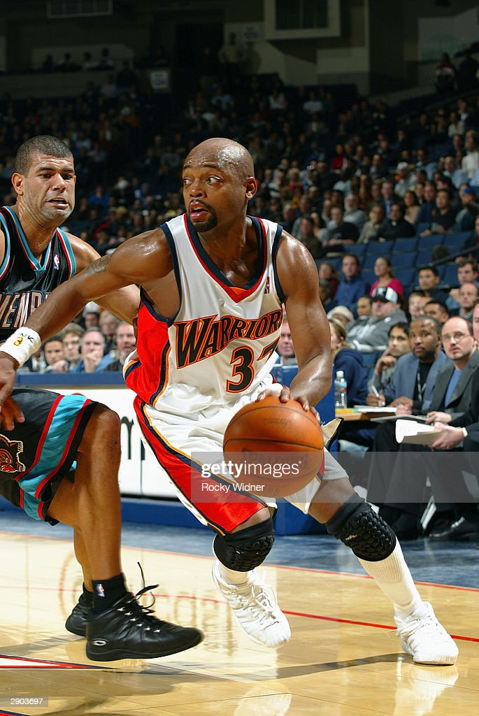Nick Van Exel #37 of the Golden State Warriors drives around Shane Battier #31 of the Memphis Grizzlies during the game at the Arena in Oakland on January 12, 2004 in Oakland, California. The Grizzlies won in double overtime 115-113.