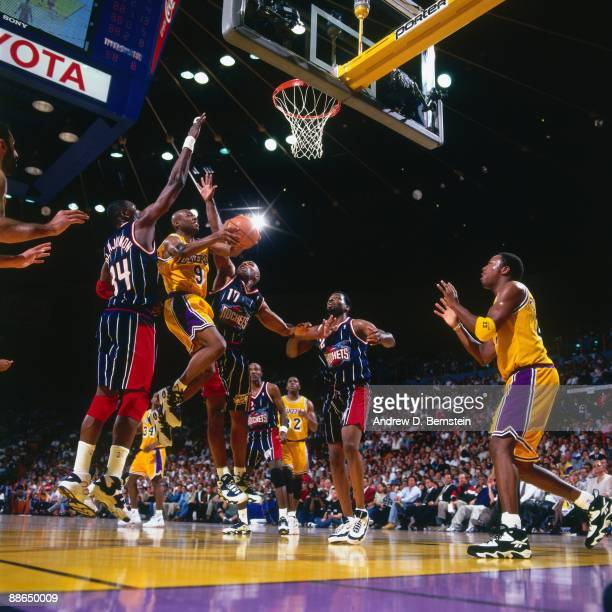Nick Van Exel of the Los Angeles Lakers goes up for a shot against Hakeem Olajuwon and Mario Elie of the Houston Rockets in Game One of the Western...