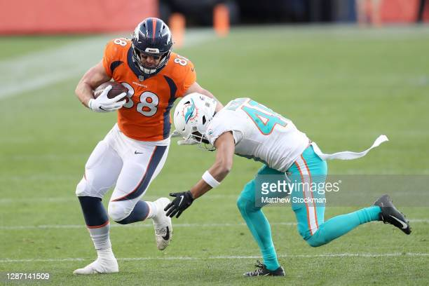 Nick Vannett of the Denver Broncos runs after his catch as he is tackled by Nik Needham of the Miami Dolphins during the third quarter at Empower...