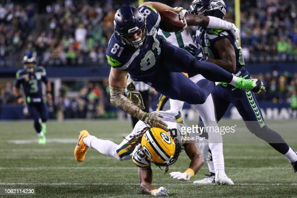 Nick Vannett of the Seattle Seahawks dives over a Green Bay Packers defender in the second quarter at CenturyLink Field on November 15 2018 in...