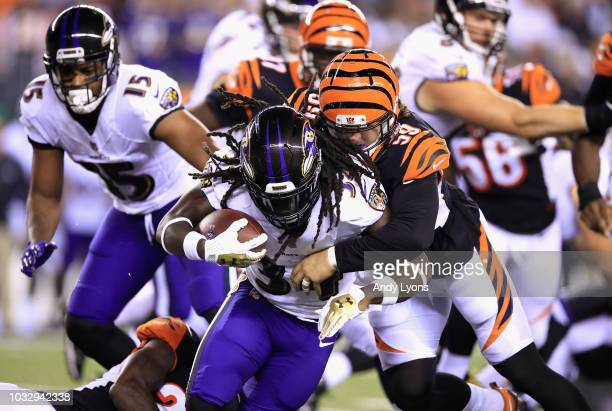 Nick Vigil of the Cincinnati Bengals tackles Alex Collins of the Baltimore Ravens during the first half at Paul Brown Stadium on September 13 2018 in...