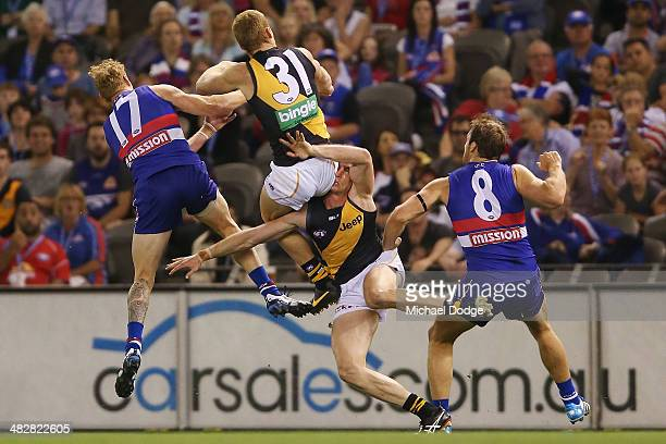 Nick Vlastuin of the Tigers collides into teamate Dylan Grimes next to Adam Cooney and Stewart Crameri of the Bulldogs during the round three AFL...