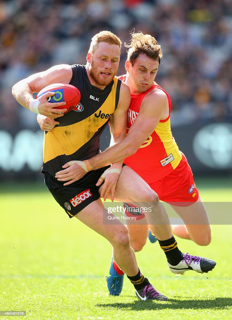 Nick Vlastuin of the Tigers is tackled by Luke Russell of the Suns during the round 20 AFL match between the Richmond Tigers and the Gold Coast Suns at Melbourne Cricket Ground on August 16, 2015 in Melbourne, Australia.