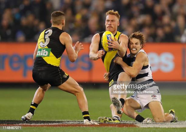 Nick Vlastuin of the Tigers is tackled by Tom Atkins of the Cats during the 2019 AFL round 12 match between the Richmond Tigers and the Geelong Cats...