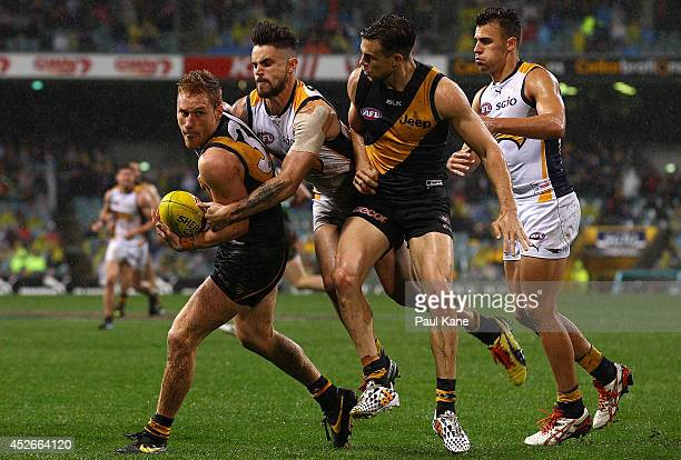 Nick Vlastuin of the Tigers looks to handball while being tackled by Ashley Smith of the Eagles during the round 18 AFL match between the West Coast...