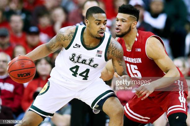 Nick Ward of the Michigan State Spartans dribbles the ball while being guarded by Charles Thomas IV of the Wisconsin Badgers in the first half at the...