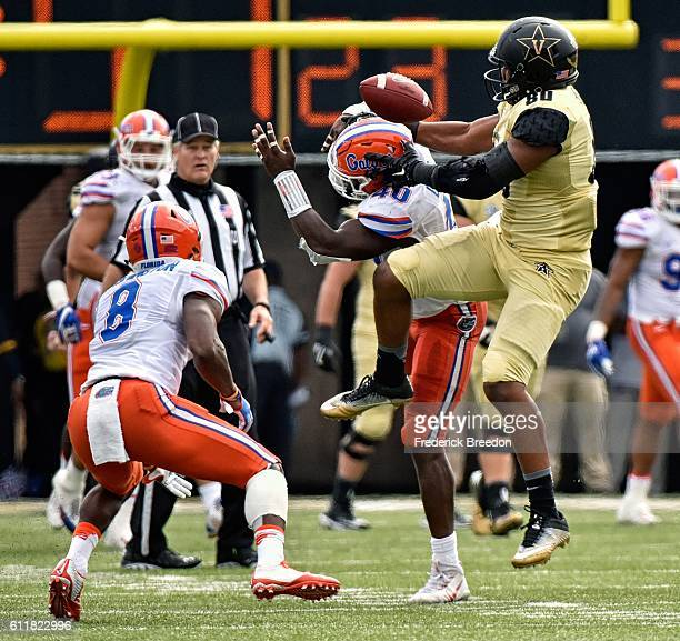 Nick Washington of the Florida Gators watches the ball bounce off teammate Jarrad Davis and Jared Pinkney of the Vanderbilt Commodores moments before...