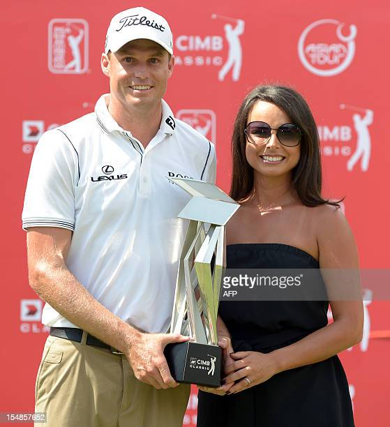 Nick Watney of the US and his wife Amber Watney pose with the trophy after winning the 61 million USD CIMB Classic golf tournament at The Mines...