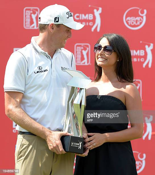 Nick Watney of the US shares a light moment with his wife Amber Watney after winning the 61 million USD CIMB Classic golf tournament at The Mines...