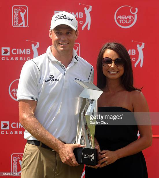 Nick Watney of USA and his wife Amber Watney pose with the CIMB Classic Trophy after the final round of the CIMB Classic at The MINES Resort Golf...